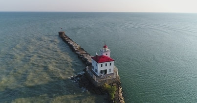 Aerial drone photograph of lighthouse surrounded by sea
