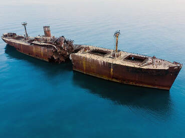 Aerial drone photograph of large boat out of service and rusting in the sea